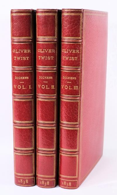 DICKENS, Charles - Oliver Twist; or, the Parish Boy's Progress. by Boz 3 vols, 24 plates [inc. Fireside plate], crimson crushed morocco by Hatchards with the original mauve cloth binding bound in at the rear of each volume, half titles present to vols 1 & 11, 4 advert pages to vol 1, 2 advert pages to vol 3, 8vo, Richard Bentley, 1838. * First edition, first issue, Eckel 59.