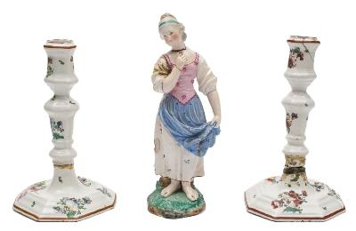 A Hochst [Damm] faience figure of a girl and a pair of Continental tin-glazed candlesticks the figure 21 cm; the candlesticks of silver shape, 19cm [badly damaged].