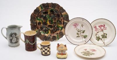 A mixed lot of late 18th/19th century pottery comprising a 'Whieldon' tortoiseshell-ware dish, 30cm [riveted]; three creamware named botanical plates; a marbled creamware mug; a slipware small mug; a pearlware jug with 'Market Lass' and 'The Tythe Pig' transfer prints; and a pearlware cottage pastille burner and cover [damages].