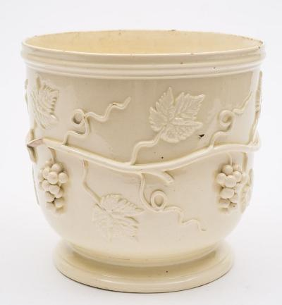 An early 19th Century Continental creamware wine cooler, applied with encircling fruiting vines, 17cm high (minor damage).