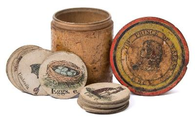 Sale BK21; Lot: 0257: ALPHABET the Prince of Wales ABC - 18 ex 26 hand coloured counters, in original cylindrical wooden lidded box with printed label.