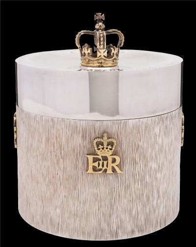 An Elizabeth II Royal Silver Wedding commemorative silver biscuit barrel, maker Carrington & Co Ltd, London 1973, the plain concave top with crown finial and inscription to rim, the body with applied silver gilt cyphers on a bark pattern reserve, numbered top base 294/1500 16.8oz.