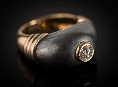 Cartier. A diamond and hematite ring the central brilliant-cut diamond approximately 0.50ct and in rub-over setting, within a hematite bombe bezel, the outer shank with French control marks, the inner shank signed and numbered '32AK040', 13gms gross weight, ring size L.