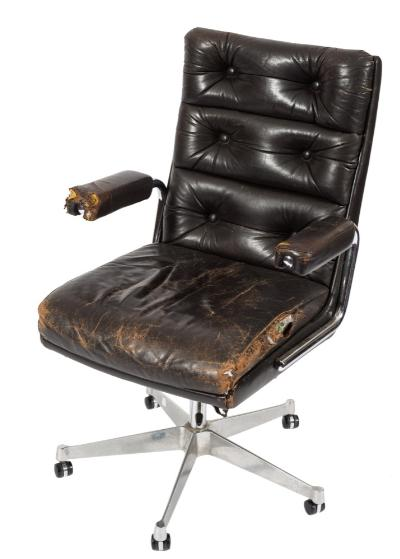 A 1960s chromium and leather revolving office armchair, with dark brown buttoned leather back, padded arm supports and seat on a chromium five splay adjustable base with castors.