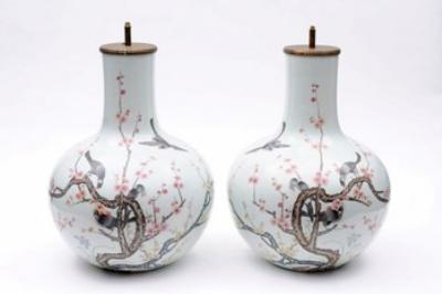 A pair of Chinese porcelain vases enamelled in the famille rose palette with magpies amongst prunus, converted as lamps, apocryphal Qianlong marks.