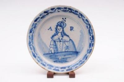Sale FS12; Lot: 0426: An English delft 'Royal Portrait' plate painted in blue with half length portrait of Queen Anne, early 18th century.
