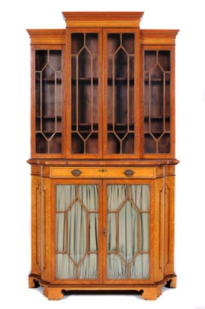 A late 19th century satinwood, burr maple and inlaid display cabinet, of shaped front outline, crossbanded in tulipwood, bordered with lines, the stepped breakfront upper part with a moulded cornice, fitted with adjustable shelves and enclosed by two pairs of astragal glazed panel doors, the lower part fitted with a frieze drawer with sliding cover and enclosed by a pair of pleated silver panel and astragal glazed doors, flanked by serpentine crossbanded and foliate decorated sides, on bracket feet, 105cm (3ft 5 1/4in) wide, 188cm (6ft 2in) high.