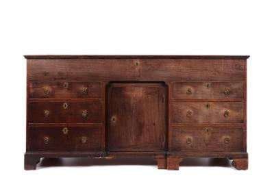A George III mahogany estate cabinet with cleated rectangular hinged top, enclosing a compartment, a similar central recessed door flanked either side by three graduated short drawers and on bracket feet, 164cm (5ft 4 1/2in) wide.