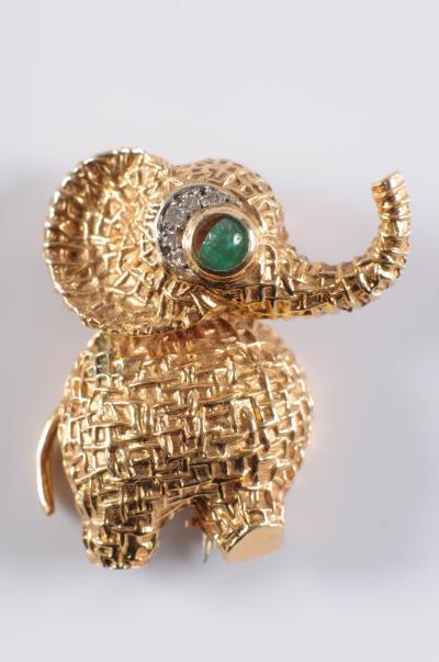 Sale FS17; Lot: 0341: Van Cleef and Arpels. An emerald and diamond novelty 'elephant' brooch with emerald and diamond-set eye, the reverse with French control marks and inscribed 'Van Cleef & Arpels 99.128 750'.