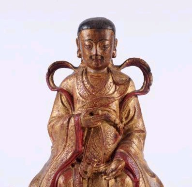 Sale FS17; Lot: 0677: An 18th century Chinese gilded metal seated deity wearing traditional costume, mounted on a wood base, some painting retouched, 34cm high.