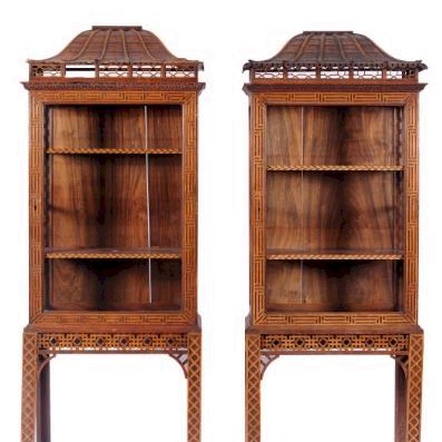 Sale FS17; Lot: 0864: A pair of carved padouk upright display cabinets on stands in the Chinese taste, with pagoda canopy and pierced fret crestings, having foliate cornices, fitted with adjustable shelves with feather inlaid edges, each enclosed by a glazed panel door with blind fret ornament, the stands with pierced fret friezes on blind fret square section legs, 75cm (2ft 5 1/2in) wide, 198cm (6ft 6in) high. Sale FS17 - 30th/31st January 2013 Illustration charge..'80.