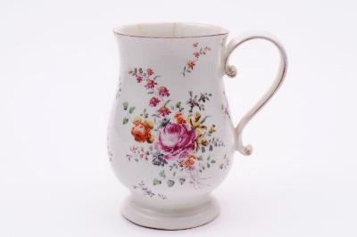 A Derby mug of baluster shape with ridged scroll handle, painted in enamels in 'cotton stem' style with a large bouquet of flowers, a smaller bouquet to the reverse, brown line rim, circa 1760, 14.5cm high, cracks to rim, handle restored.