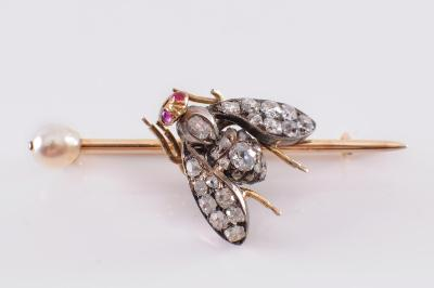 A ruby, diamond and pearl insect bar brooch the thorax, abdomen and wings pave-set with old brilliant-cut diamonds, the head with two cabochon ruby eyes on a bar brooch with single pearl.