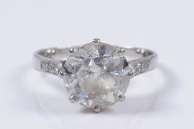 A diamond mounted single stone ring with round old brilliant cut diamond approximately 9.8mm x 5.1mm estimated to weigh 3cts in a curtain claw setting between diamond three stone shoulders.