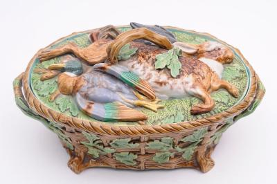A Minton majolica game pie dish and cover of oval form the base moulded as an oak embellished basket, the cover with a hare, mallard and water fowl on a bed of ferns and oak leaves, 32cm long, impressed Minton, 668 with datecode for 1864.