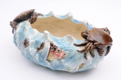 A Delphin Massier (Vallauris) majolica bowl of oval wave moulded form modelled with a spiny fish flanked by crabs and verso with sardine-like fish, 37cm long, painted Delphin Massier Cie, Vallauris, AM, late 19th century, cracked.