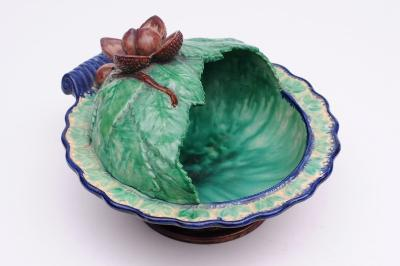 A St Honore pottery chestnut basket of circular leaf moulded and partially domed form with scroll handle, the top naturalistically modelled with nuts picked out in brown on a green and blue edged ground, 30cm long, impressed St Honore, late 19th century, restoration to dome.