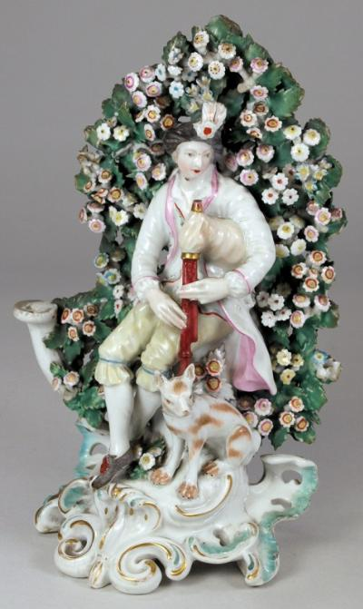 A Derby porcelain candlestick group modelled as a musician seated before a flowering bocage in plumed hat playing the bag pipes with a hound at foot, on pierced scrollwork base, 20.5cm high, patch marks, circa 1770, devoid socket.
