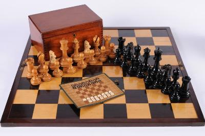 The British Chess Company, a boxwood and ebony Staunton pattern competition chess set the knights as horses with xylonite heads, the king 10.5cm high, the pawn 5.5cm high, contained in a polished mahogany box bearing the British Chess Company< Stroud, Glos, label No 1s printed label, together with a folding rosewood and boxwood chess board, stamped British Chess Company, Stroud, Glos, 59 x 59cm and a travelling pocket chess set in folding canvas wallet, (one white rook missing).