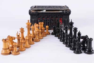 An early Jaques boxwood and ebony Staunton pattern chess set the white king stamped J Jaques, London to the base rim, 9cm high, the pawn 4.25cm high, contained in a Cartonpierre box of pierced castellated design bears printed paper label with Entered No 204, 21cm wide some damage.