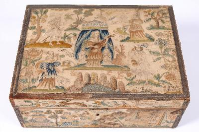 A 17th century needlework box of rectangular outline, the lid decorated with a central figure of a lady playing a lute under a canopy, a lady holding a mirror another holding a flower, a gentleman holding fruit and another holding a bird, surrounded by birds, insects, stag and hound, the sides depicting biblical scenes including Hagar praying for water, the sacrifice of Issac, Rebecca at the well, surrounded by a camel, butterflies, hares, snails and insects, each panel enclosed by metal thread borders, 38cm wide, 14.5cm high and 28.5cm deep. To be collected.