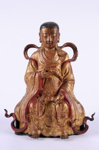 An 18th century Chinese gilded metal seated deity wearing traditional costume, mounted on a wood base, some painting retouched, 34cm high.