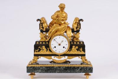 Sale FS17; Lot: 0742: L'Echopié Jne à Paris, a bronze, ormolu and marble mantel clock the eight-day duration movement striking the hours on a bell with an outside countwheel, the white enamel dial signed L'Echopié Jne à Paris, with black Roman numerals and decorative brass hands, the three tier bronze case with raised relief to the front depicting children playing instruments within a field, with goats to the case sides and floral swags set below, standing on ormolu cloven supports, surmounted by a suckling baby with mother, possibly Apollo with the Goddess Leto, seated on a classical day bed with ormolu griffin supports to the four corners, standing on a further green marble base with ormolu mounts to the edges and turned feet, height: 45cm.