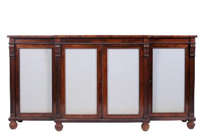 Sale FS17; Lot: 0826: A Regency rosewood breakfront side cabinet, applied with beaded mouldings, the four doors inset with fabric panels and divided by moulded uprights, headed by scrolls and on reeded bun feet, 183cm (6ft 0in) wide.