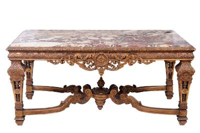 Sale FS17; Lot: 0850: A 19th Century French carved giltwood centre table in the Louis XIV taste, surmounted by a rectangular panel of breche violette marble, within a foliate border, the cushion frieze decorated with foliage and with shaped and pierced acanthus and paterae aprons, on openwork square section tapered legs with acanthus leaf husk and paterae ornament, united by curved acanthus scroll stretchers with central finial, the top 165cm (5ft 5in) x 85cm (2ft 9 1/2in).