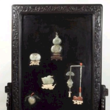 Sale FS18; Lot: 0686: A Chinese hardstone-inlaid lacquer and hardwood screen and stand the black lacquer rectangular panel inlaid with a double gourd vase, a peach spray, a duck, two hanging plaques and a peaches and bat carving, the frame carved overall with archaistic scrollwork and stylised lotus, total height 103cm, total width 67cm, some restoration and minor damage.