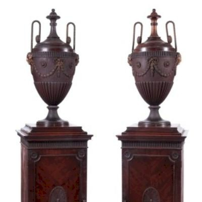 Sale FS18; Lot: 0813: A pair of George III mahogany pedestal urns, being zinc lined and ormolu mounted, the detachable covers with beaded and paterae decorated handles and beaded finials, the half reeded bodies with fluted bands and applied masks of the devil, ribbon tied husk garlands and circular fluted and beaded paterae, the pedestals below with fluted friezes, one lead lined, the other fitted with three short drawers, each enclosed by a moulded panel door with central oval paterae and circular paterae spandrels and raised on a plinth, 172cm (5ft 6in) high.