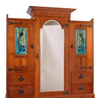 Sale FS18; Lot: 0856: By Shapland & Petter, Barnstaple a late Victorian/Edwardian oak wardrobe in the Art Nouveau taste, applied throughout with beaten patinated metal strap hinges and knobs, the raised pediment above an arched mirrored door, flanked by two panelled doors each inset with a tile picture depicting a peacock, an arrangement of six drawers below and on bracket feet, 180cm (5ft 11in) wide, 216cm (7ft 1in) high, the brass locks all impressed S & P B, the tiles marked Flaxman on the reverse.