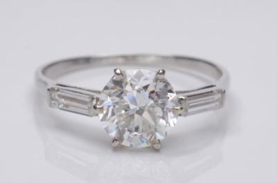 Sale FS18; Lot: 0292: A diamond single-stone ring with circular, brilliant-cut diamond approximately 8.1mm x 5.2mm estimated to weigh 2.2cts in a six-claw setting between baguette-cut diamond single-stone shoulders.