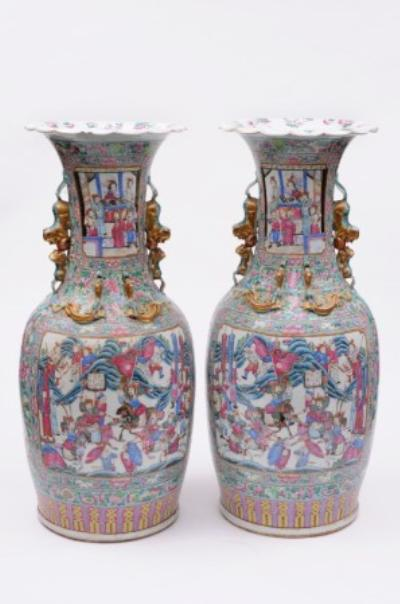 A pair of large Canton famille rose porcelain vases of shouldered oviform, the flaring necks applied with chilong and buddhistic lion and cub handles, enamelled with panels depicting scenes at court and warriors on a turquoise ground profusely decorated with fruit, birds, butterflies, flowers and foliage, late 19th century, 78cm high.