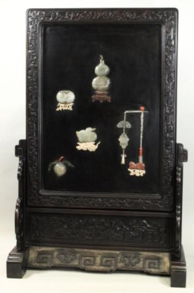 A Chinese hardstone-inlaid lacquer and hardwood screen and stand the black lacquer rectangular panel inlaid with a double gourd vase, a peach spray, a duck, two hanging plaques and a peaches and bat carving, the frame carved overall with archaistic scrollwork and stylised lotus, total height 103cm, total width 67cm, some restoration and minor damage.