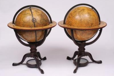 Sale FS18; Lot: 0756: ADAMS, Dudley (1762-1830) a pair of Regency 12 ins terrestrial and celestial table globes the terrestrial globe inscribed 'This new globe of the Earth correctly laid down according to ye best observations & latest discoveries, Dudley Adams, Fleet Street, London, 1807', the gores hand coloured in outline, marking the tracks of the second and third voyages of James Cook and Anson's voyage; the celestial globe inscribed 'This new celestial globe containing all ye Southern Constellations lately observed at the Cape of Good Hope and all the stars in Flamstead's British Catalogue, Dudley Adams, Fleet Street, London 1809. The gores decorated with constellation figures, named in Latin and English, mounted on mahogany tripod stands, the legs united by an undertier incorporating a compass, 2ft (61cm) high.