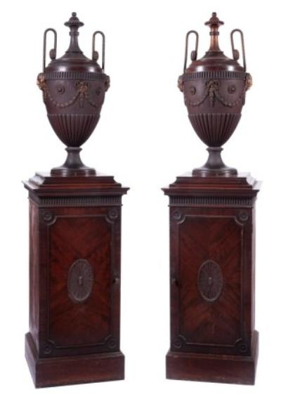 A pair of George III mahogany pedestal urns, being zinc lined and ormolu mounted, the detachable covers with beaded and paterae decorated handles and beaded finials, the half reeded bodies with fluted bands and applied masks of the devil, ribbon tied husk garlands and circular fluted and beaded paterae, the pedestals below with fluted friezes, one lead lined, the other fitted with three short drawers, each enclosed by a moulded panel door with central oval paterae and circular paterae spandrels and raised on a plinth, 172cm (5ft 6in) high.