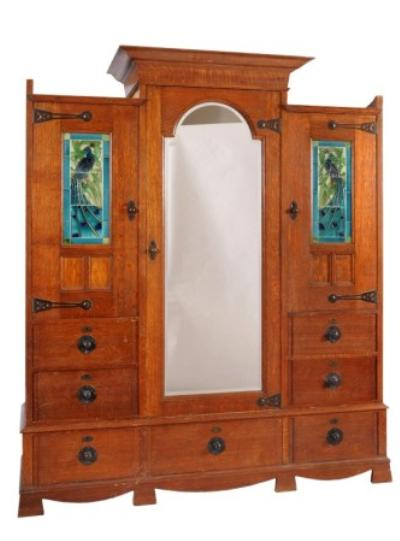 By Shapland & Petter, Barnstaple a late Victorian/Edwardian oak wardrobe in the Art Nouveau taste, applied throughout with beaten patinated metal strap hinges and knobs, the raised pediment above an arched mirrored door, flanked by two panelled doors each inset with a tile picture depicting a peacock, an arrangement of six drawers below and on bracket feet, 180cm (5ft 11in) wide, 216cm (7ft 1in) high, the brass locks all impressed S & P B, the tiles marked Flaxman on the reverse.