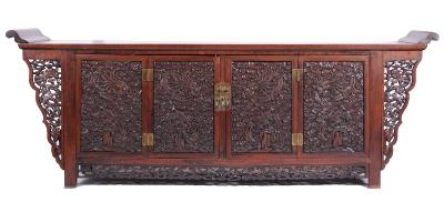 A Chinese carved hardwood altar cabinet, the plain rectangular top with shaped moulded ends, the quadruple panel front elaborately carved with dragons amidst cloud bands, the two centre panels as enclosing doors, flanked by similarly decorated shaped ends, the pierced cloud band apron base, on block feet, 267.5cm (8ft 9 1/4in) length, 51cm (1ft 8in) depth, 99cm (3ft 3in) height.