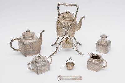A Chinese five piece silver tea set, early 20th century, comprising; kettle on stand with burner, teapot, sugar bowl with cover, cream jug and tea canister, with square bodies, decorated with bamboo, the handles of simulated bamboo, together with a pair of sugar tongs and tea strainer, all with character marks, together with the original bill of sale from Tow Mow Shing (silversmith), 3rd May 1922, height of kettle and stand 30cm, total weight 73ozs.