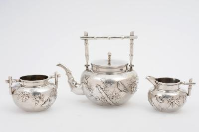 A Chinese silver three piece tea service, maker Wang Hing & Co, Hong Kong. The teapot with rectangular bamboo shoot handle, the body decorated with finches amongst bamboo, with similar decoration to the cream jug and sugar basin, total weight of silver 2730ozs.