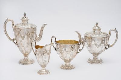 A Victorian four piece silver tea and coffee service, maker Martin Hall & Co Ltd, London, 1874, of classical vase form, with engraved and embossed decoration of cherub masks, floral and ribbon swags above a border of stiff chased leaves and leaf capped loop handles, the covers with pineapple finials, height of the coffee pot 28cm, total weight 90ozs.