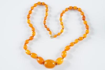 A graduated amber bead single string necklace graduated from 10mm x 7mm, to 29mm x 23mm, 41.8gms gross weight, together with two small loose beads.