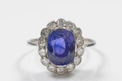 A sapphire and diamond mounted oval cluster ring, the central cushion shaped sapphire approximately 10mm long x 7.5mm wide, within a surround of round, brilliant cut diamonds, ring size 'M'.
