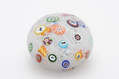 A Baccarat dated spaced millefiori paperweight set with a variety of coloured and butterfly canes and eight animal silhouettes comprising two cockerels, stag, elephant, horse, monkey, dog and goat and on the flank 'B 1848' on a bed of diced white latticinio tubes, 7.5cm diameter.