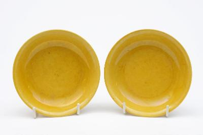 A pair of Chinese yellow glazed small saucer dishes each with shallow curving sides and everted rim, apocryphal underglaze blue six-character Jiajing marks, 11.5cm diameter, one with two haircracks to rim.