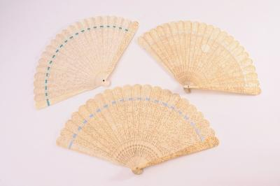 A 19th century Chinese brise fan, the sticks carved to both sides with figures in a garden landscape, with similar decoration to the guards, 21cm long and two similar single sided carved ivory brise fans, each 19cm long.