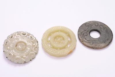 A group of three Chinese jade and hardstone pendants/discs, including a celadon jade pendant/brooch with articulated centre, carved and pierced with scrolling foliage, white metal mount, 6cm; a similar hardstone disc carved and pierced with raised beads, 6cm; and a grey stone disc carved with a chilong and scrolls, 6cm [chipped].