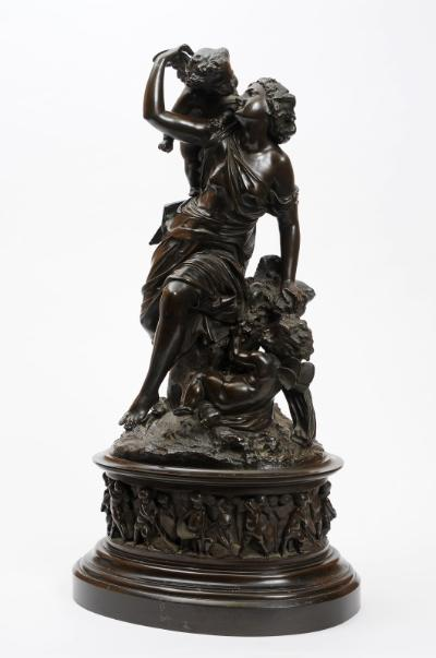 After Moreau, a bronze figure group depicting a neo-classical maiden being taunted by two cherubs, on a naturalistic base, mounted on an oval plinth decorated with putti harvesting corn, dark brown patination, signed Moreau, 79cm high.