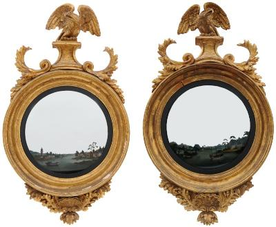 A rare pair of Regency carved giltwood and Chinese reverse painted convex mirrors, each surmounted by a figure of an eagle with outspread wings on a plateau, flanked by acanthus scrolls, the mirror plates reverse painted with river and estuary scenes, with boats and with pagodas and other buildings on the banks and mountains beyond, framed by ebonised slips and moulded and reeded surrounds, having central shell ornament below within oak leaves and acorn surround, 113cm (3ft 8 1/2in) x 65cm (2ft 1 1/2in).